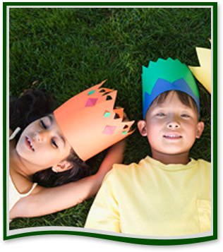 Students wearing paper crowns sit on grass