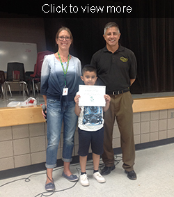 Two adults pose with young male student of the month
