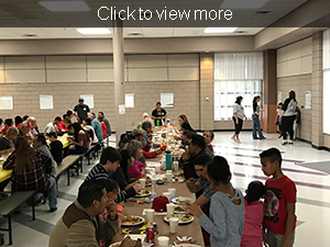 Community members eat Thanksgiving dinner at a long table