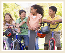 Four students pose outside with bikes, a skateboard and helmets