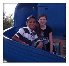 Students pose on a playground slide