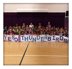 Students and teachers pose with a YESO Thunderbirds sign