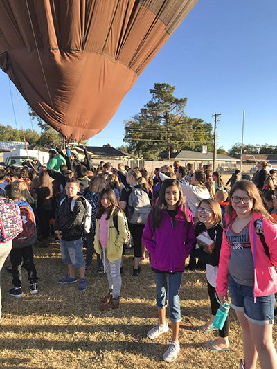 Students stand in front of a hot air balloon