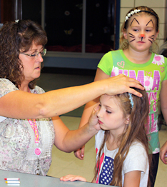 Female student gets her face painted by an adult