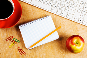 A cup of coffee, a keyboard, paper clips, a notebook, a pencil and an apple sit on a desk
