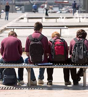 Students with backpacks sit on a bench