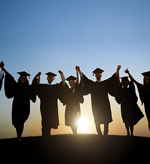 Graduates hold hands on a hill as the sun rises