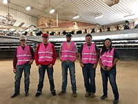 Four staff members in pink vests stand together