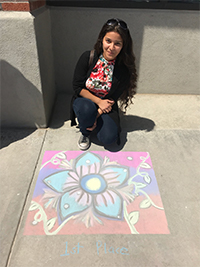 Staff member kneels behind flower chalk art