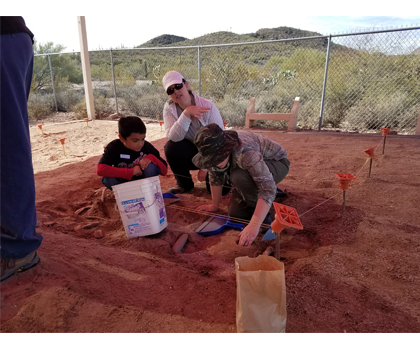 Students and staff digging in soil