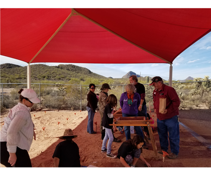 Adults and student screening soil under tent