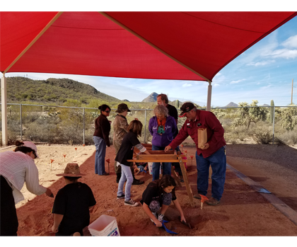 Adults and students working with soil under tent