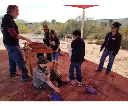 Adults and students working with soil