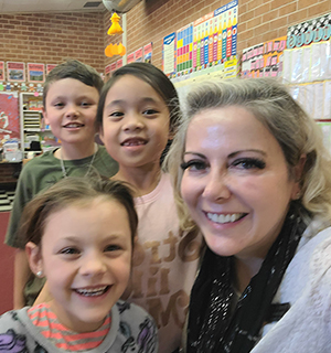 Three happy elementary students posing for a picture with a female adult
