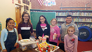 Group of six smiling elementary students standing in front of an activity table