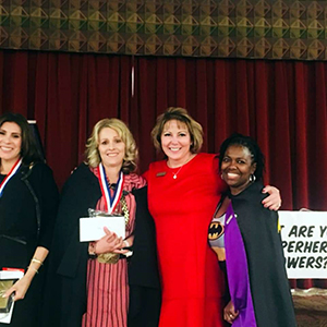 Teacher of the Year, Kelly Zamudio pictured with two other women on stage