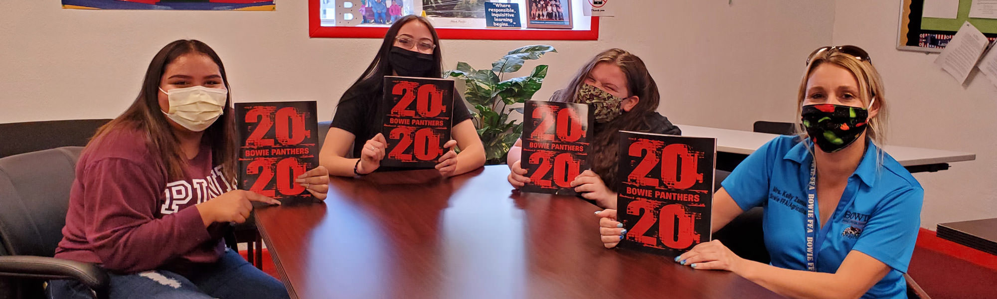 Students and an adult holding 2020 yearbooks