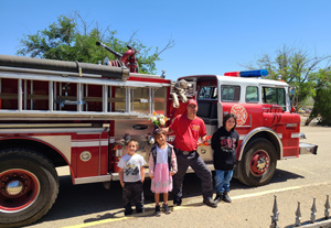 fireman and students standing in front of fire truck