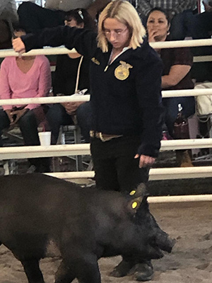 student with her pig at the fair