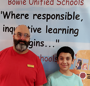 Luciano Moreno poses with staff member Travis Beck in front of a Bowie Unified Schools sign