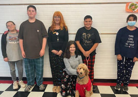 Six students and a dog dressed in pajamas