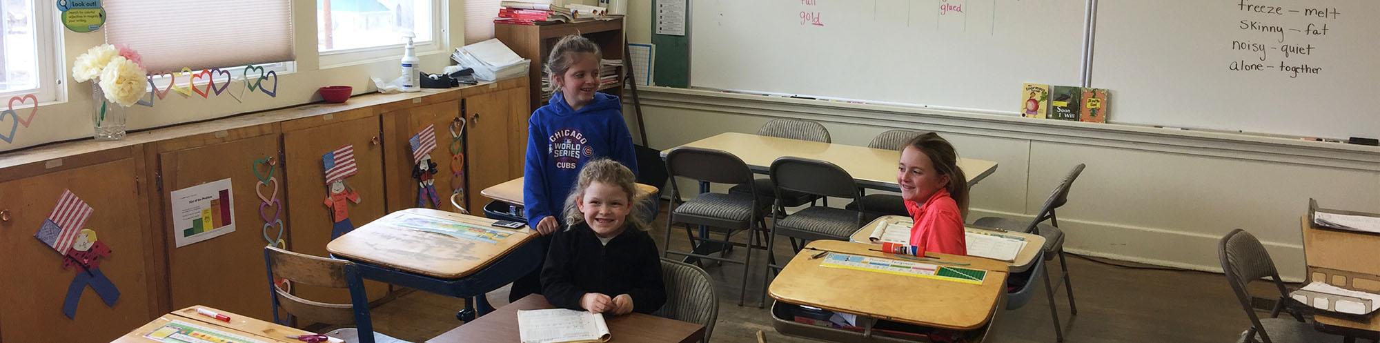Three happy elementary school girls sitting in a classroom
