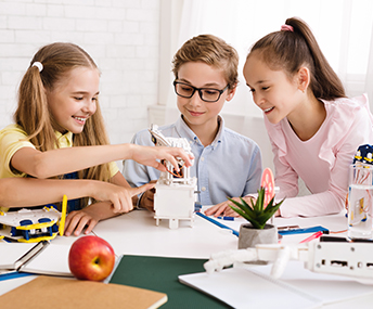 Three happy students working on a project together