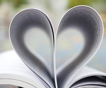 An open book with pages folded in shape of heart