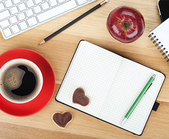 Desk with laptop, red mug full of coffee, and a notepad