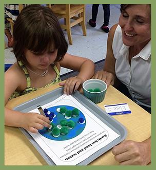 Teacher helps a student with a pom pom project