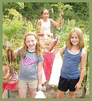 Students hold carrots pulled from a garden