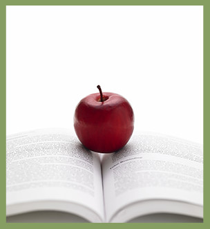 Apple sitting in the center of an open book