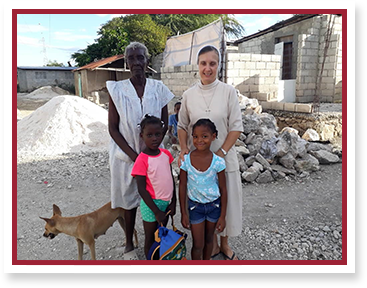 Sister poses with people in Haiti