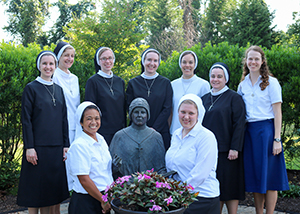 Group of nuns with a statue and flowers