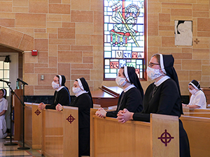 Sisters wearing masks and sitting in the church