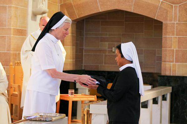Sr. Justine Reina receives her veil and crucifix from Sr. Barbara Thomas, ASCJ, Provincial Superior