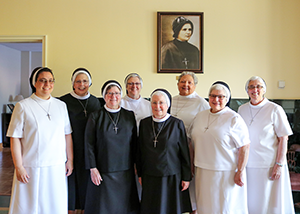 Group of women pose together in front of a framed picture of Mother Clelia Merloni