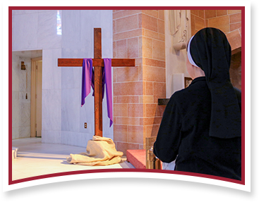 Sister praying in front of Cross