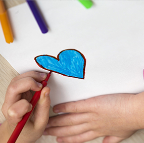 young student's hand drawing a heart on paper