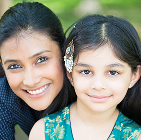 Close-up of mother and daughter smiling for a picture