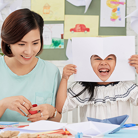 Teacher next to laughing student with heart cut-out