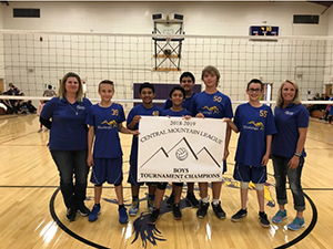 Boys volleyball team holding up a tournament champion banner