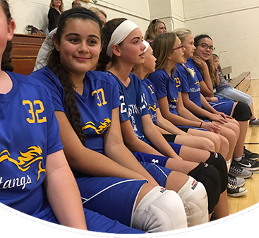 Female sports team members pose on a bench