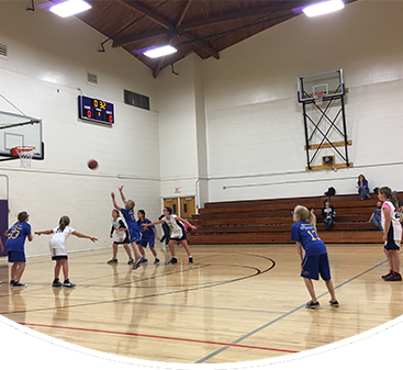 Students play basketball in a gym