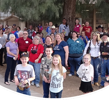 Group of students, staff and family members pose together outside