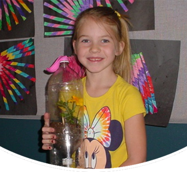 Female student poses with a terrarium made out of a water bottle