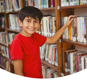 Male student stands near books in a library