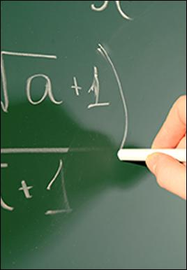 Hands write on a blackboard using chalk