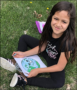 Smiling female student coloring in a drawing of the earth as she sits outside on the grass