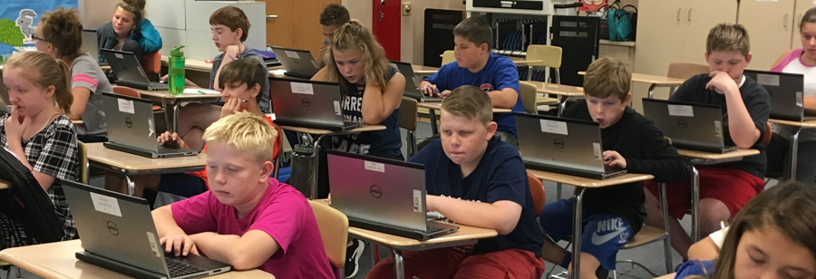 Group of students working on laptops at their desks